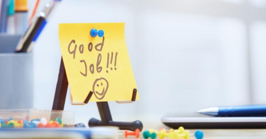 Bàn có bút, đinh ghim, máy tính bảng và ghi chú dán có chữ: Công việc tốt