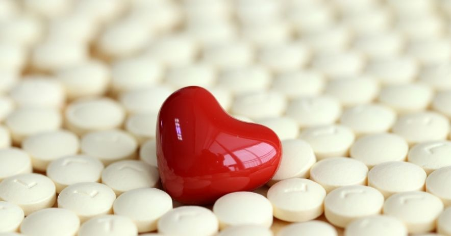 A sea of round white pills surround a red pill shaped like a heart.