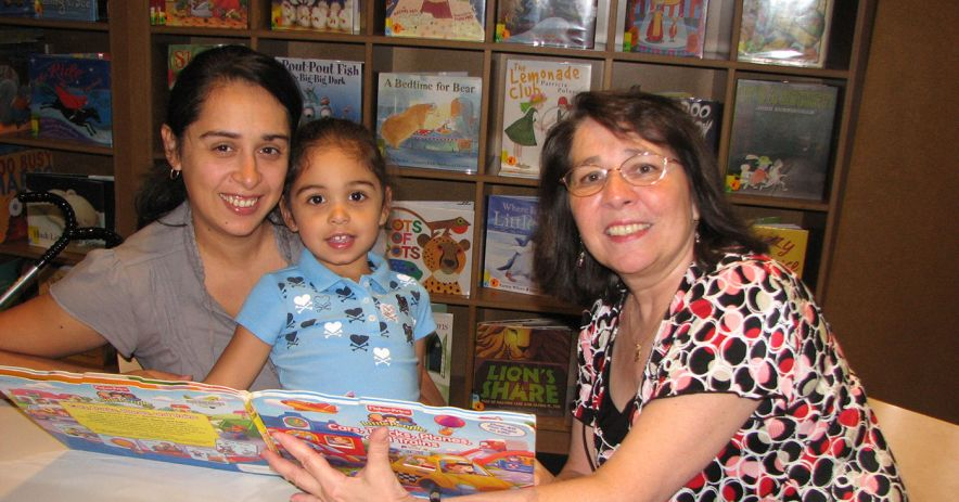 adult reads picture book to a child with her parent