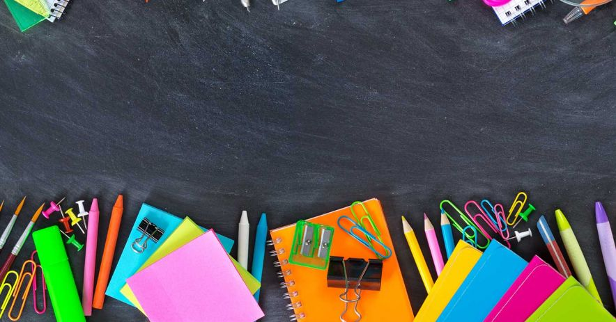 2 rows of colorful schools supplies lying on a chalky blackboard
