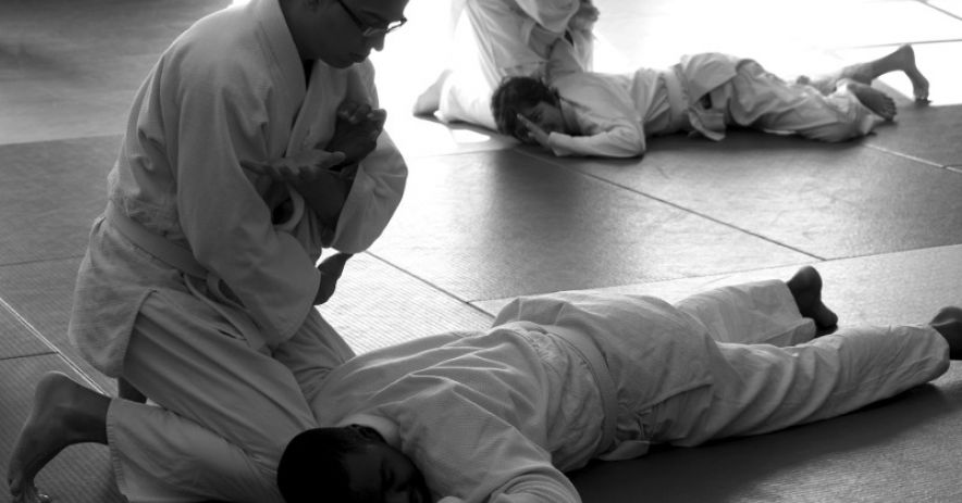 Two pairs of martial artists practice self defense on mats.
