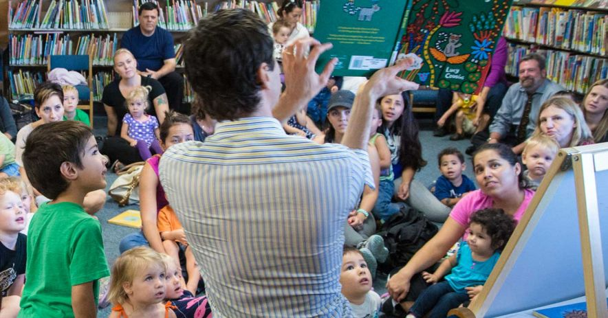 Crowd of children gathered around a seated man reading 'Jazzy in the Jungle'