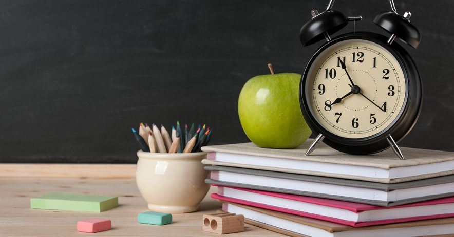 Alarm clock and green apple sitting atop a stack of books with colored pencils and erasers scattered on a desk and a chalkboard behind.
