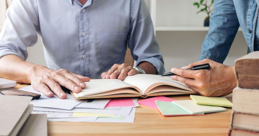 Hai người học sách giáo khoa và ghi chép.