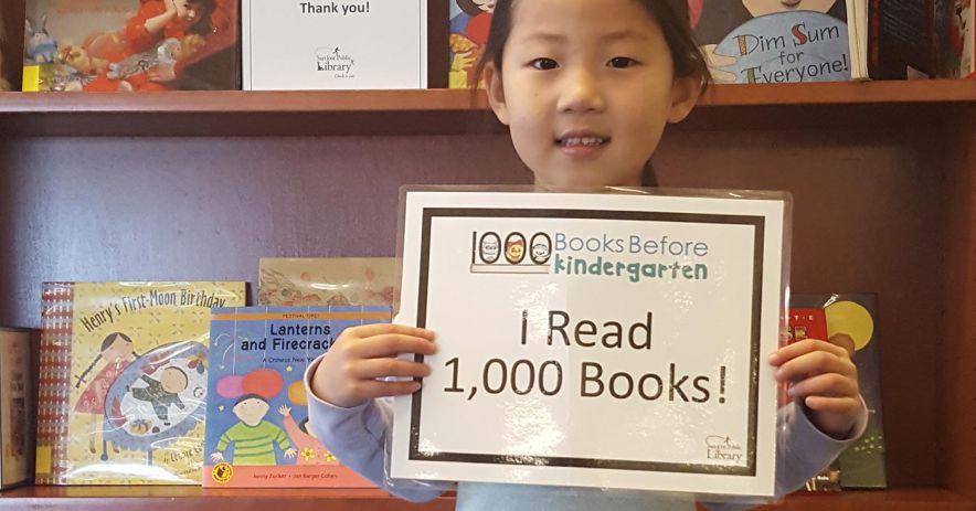 niña sosteniendo un cartel, 'Leí 1,000 libros'