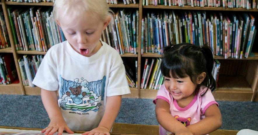 Surprised young boy and giggling younger girl looking at books.