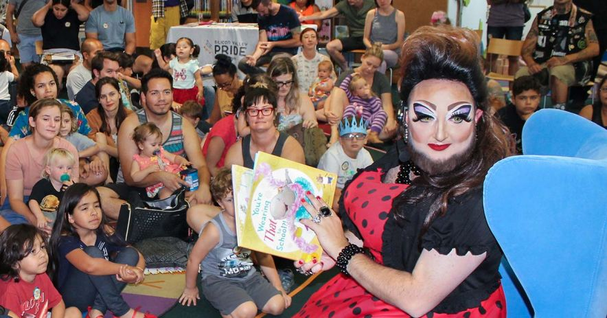 Drag Queen Talon Marks reading a story to a large crowd of children and parents.