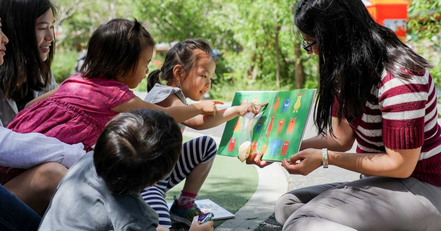 Librarian reading picture book to gathered children at a playground.