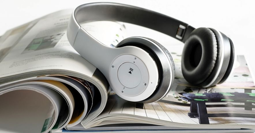 Headphones sitting atop an open magazine.