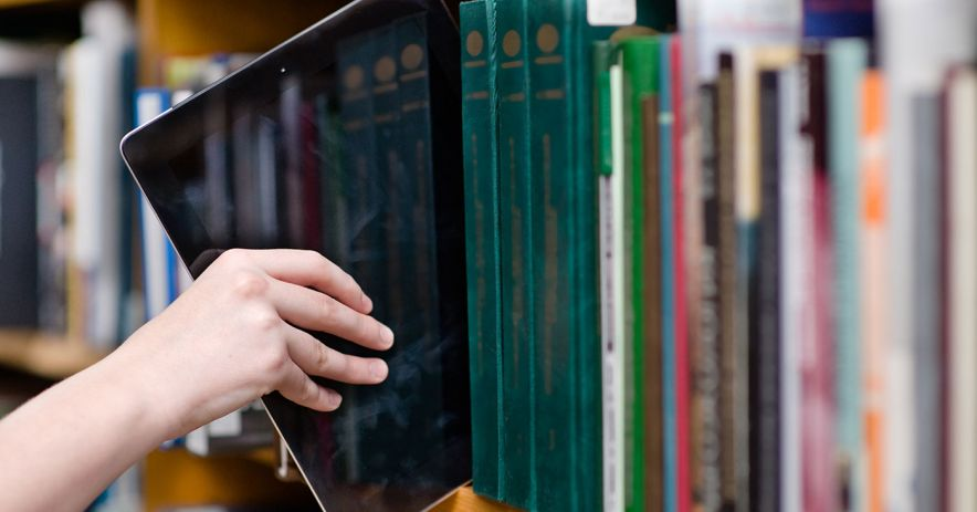 Hand pulling a large tablet off of a shelf of books.