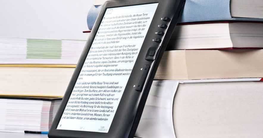 eReader device resting against a pile of books.