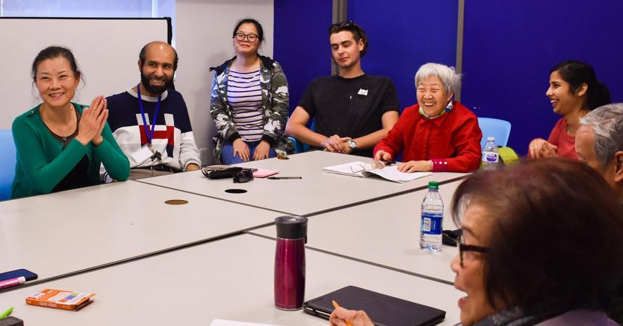 Group of diverse adults seated around a table laugh during an ESL Conversation Club.