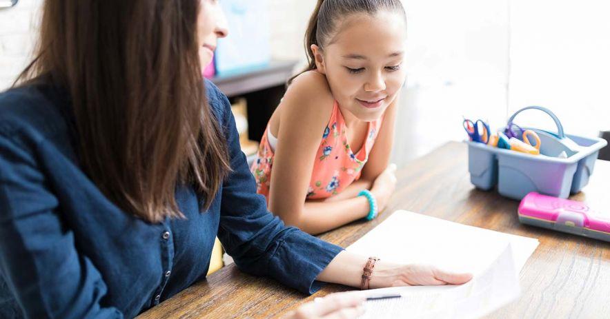 Gia sư và cô gái trẻ thảo luận về bài tập về nhà.
