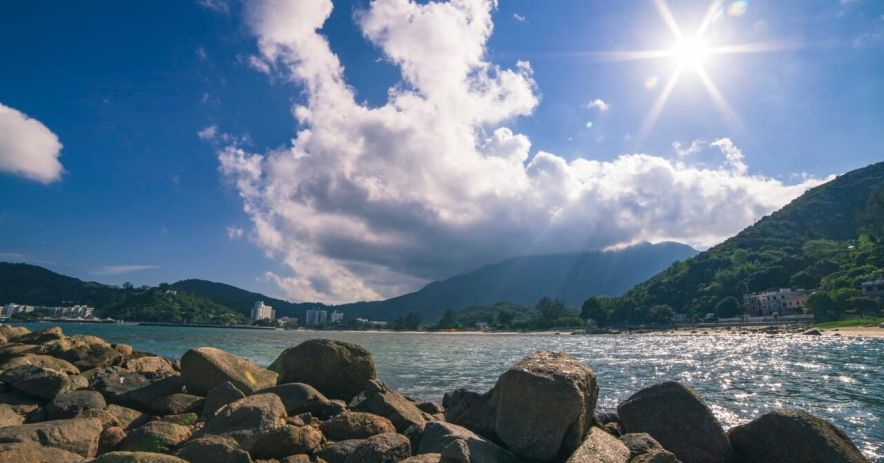 Looking out onto a bay with rocks on the shore of the photographer, and mountains/buildings on the far side of the bay; the sky is blue with bright sunshine and puffy clouds