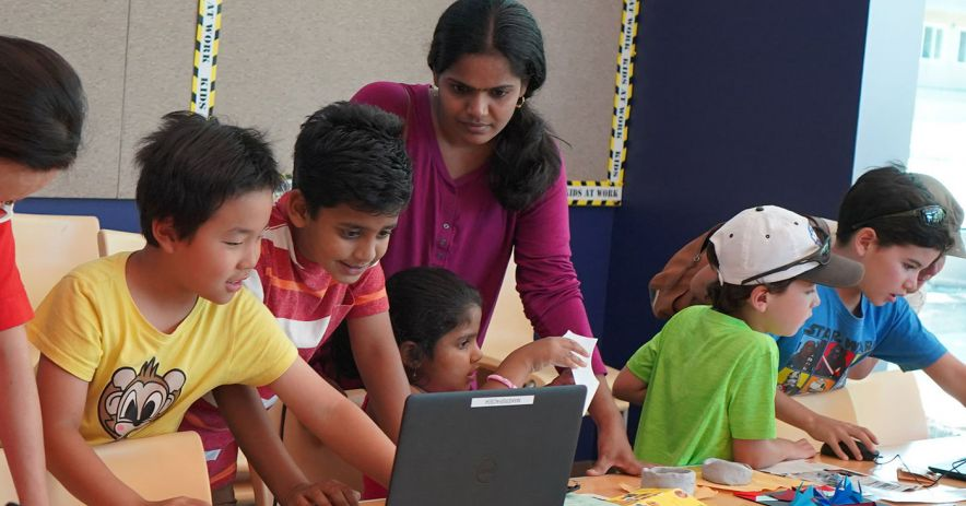 Children and mentors work on laptops at a coding program.