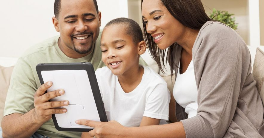 A family looks at an eBook on a tablet together.
