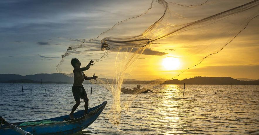 Fisherman casting out net at sunset.