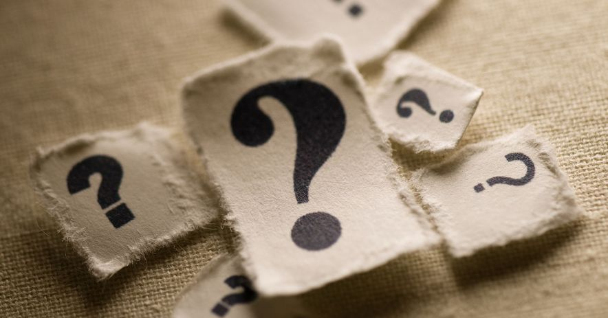 Question marks on torn pieces of parchment.