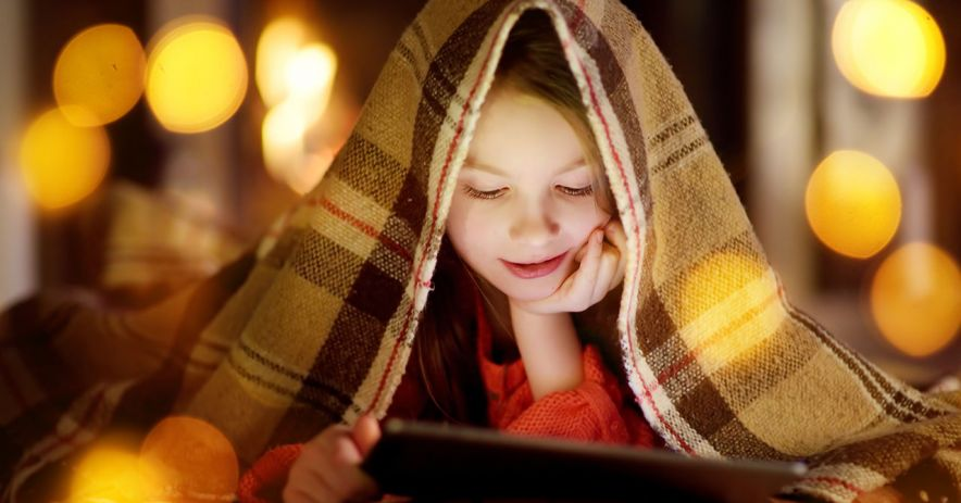 Girl under a blanket reading a tablet at night.