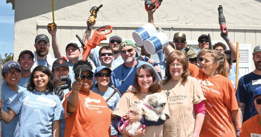 Large group of enthusiastic Rebuilding Together volunteers with tools on a construction site.