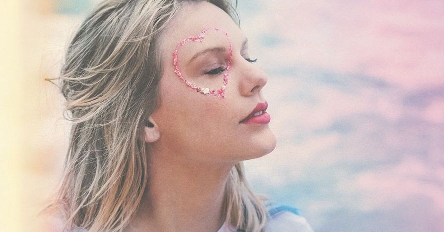 Taylor Swift with a glitter heart around her eye on a rainbow cloud background