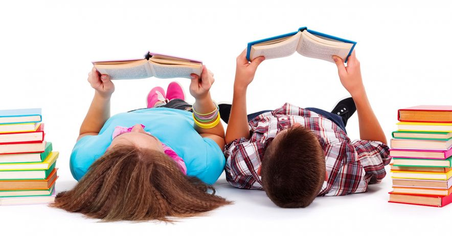 Teen girl and boy lying on their backs reading books.