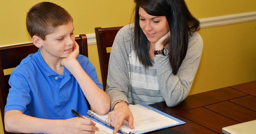 Gia sư tình nguyện giúp trẻ làm bài tập về nhà.