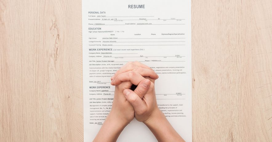 Folded hands rest atop a printed copy of a resume.