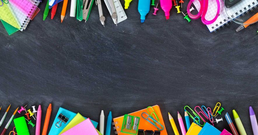 Array of colorful school supplies on a blackboard.