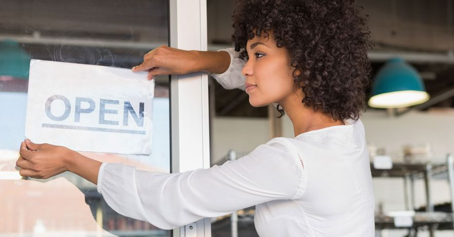 A business owner affixes an open sign to the door of her new modern, clean, stylish new business.