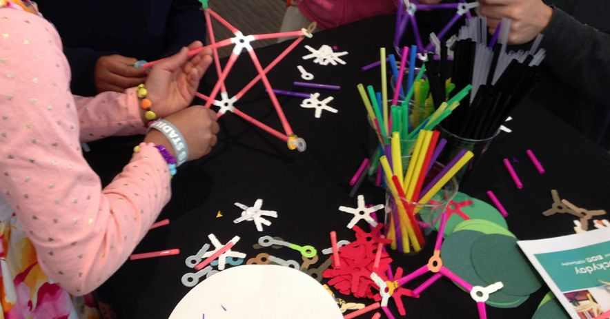 Children constructing geometric objects with straws.