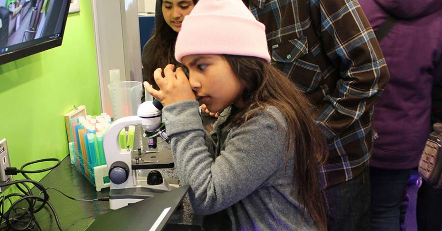 Girl looking in microscope at STEM program supported by the Foundation.
