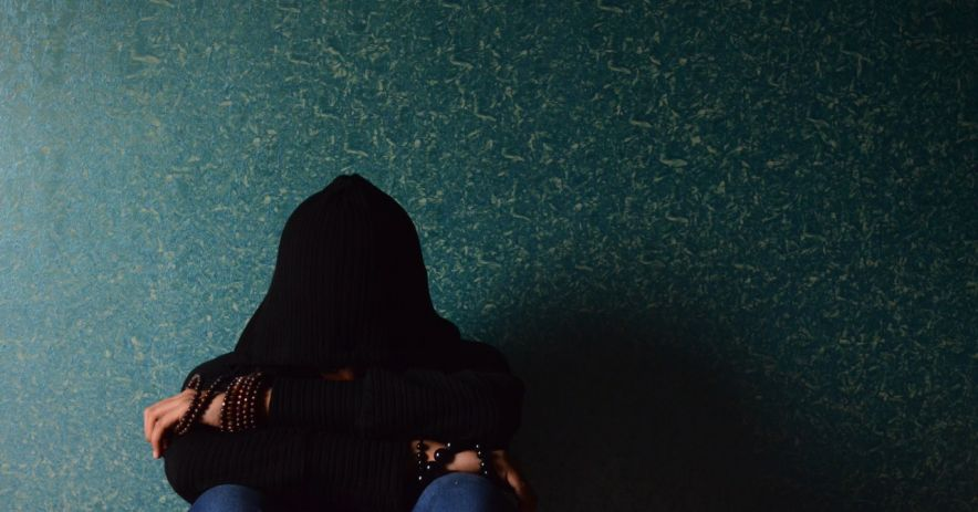 Teen in a hoodie sitting crumpled in front of a wall.