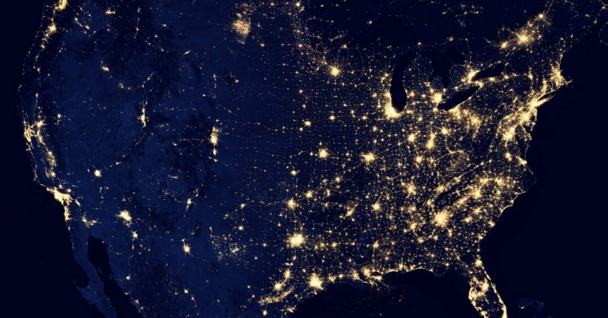 An aerial view of the United States lit up around the the country at night.