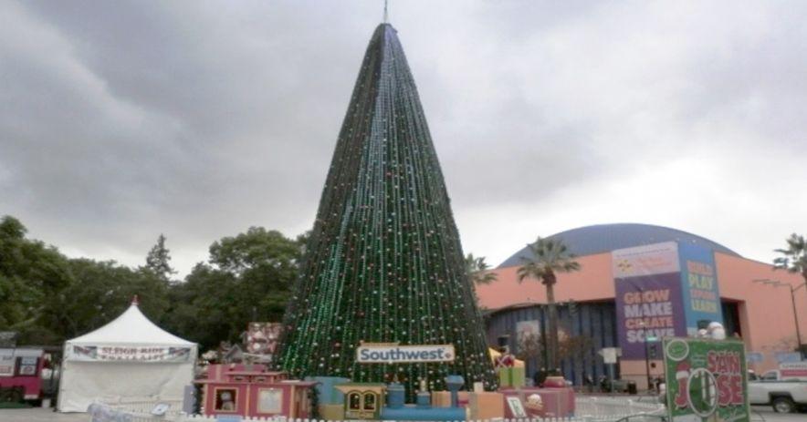 Navidad en el parque Árbol de Navidad con el logo de Southwest Airlines. El árbol está rodeado por un tren y una valla de metal blanco.