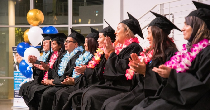 SJPL's Career Online High School graduates applaud a speaker while wearing caps, gowns, and beautiful lei garlands
