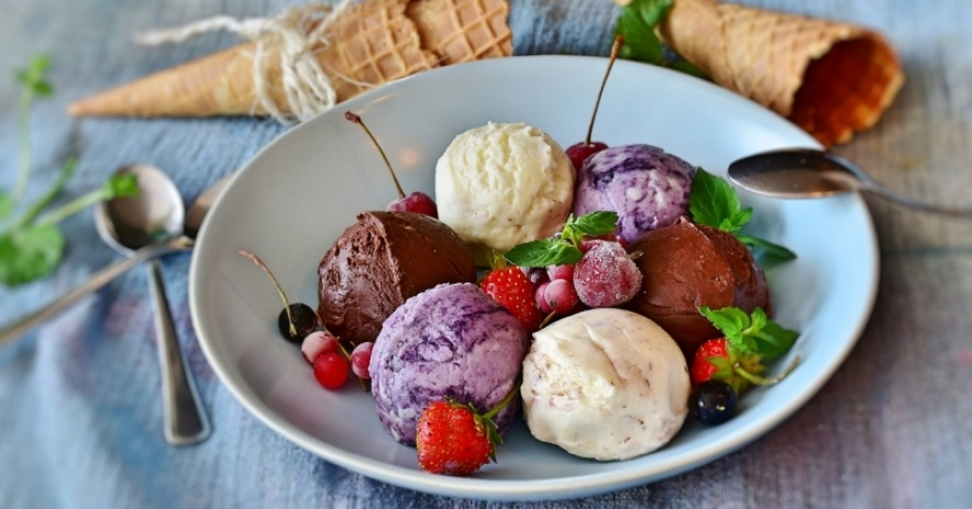 Three types of ice cream in a bowl with frozen berries and mint, sitting on a blue cloth-covered table with empty ice cream cones