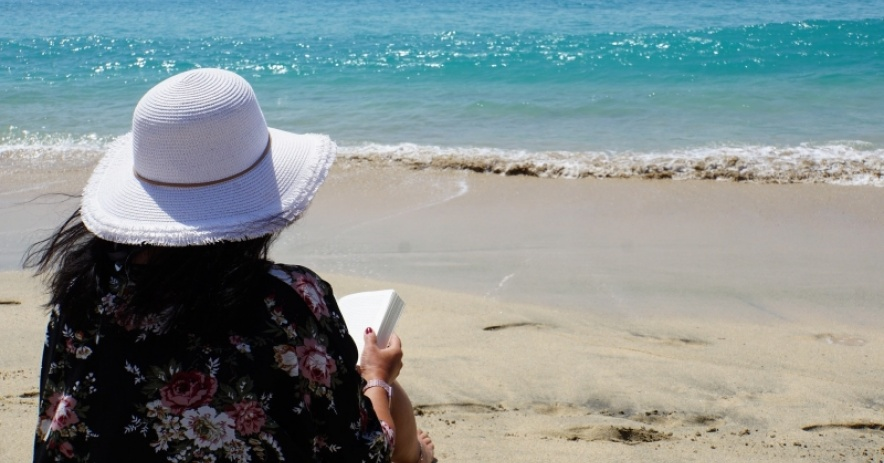 Image of woman wearing a white hat, sitting on the beach with a book