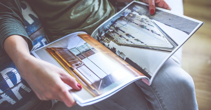 A person is shown reading a magazine containing architectural and interior design images.