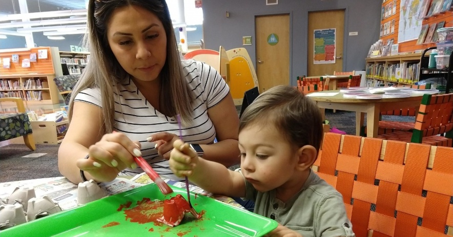 A parent helps her child paint the red part of what will be a Very Hungry Caterpillar.