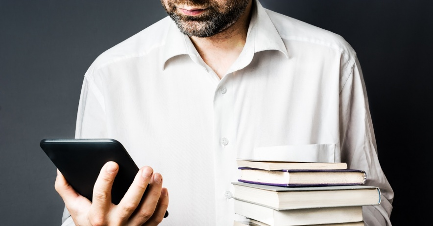 Man holding a stack of print books in his right hand and looking at an eBook eReader in his left hand