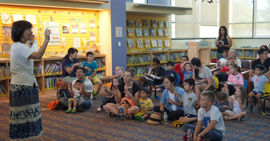 Seated children and caregivers listen to storytime at the library.