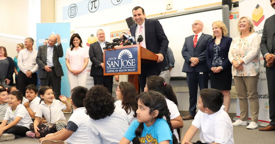 Children sit as City officials give a press conference at a school.