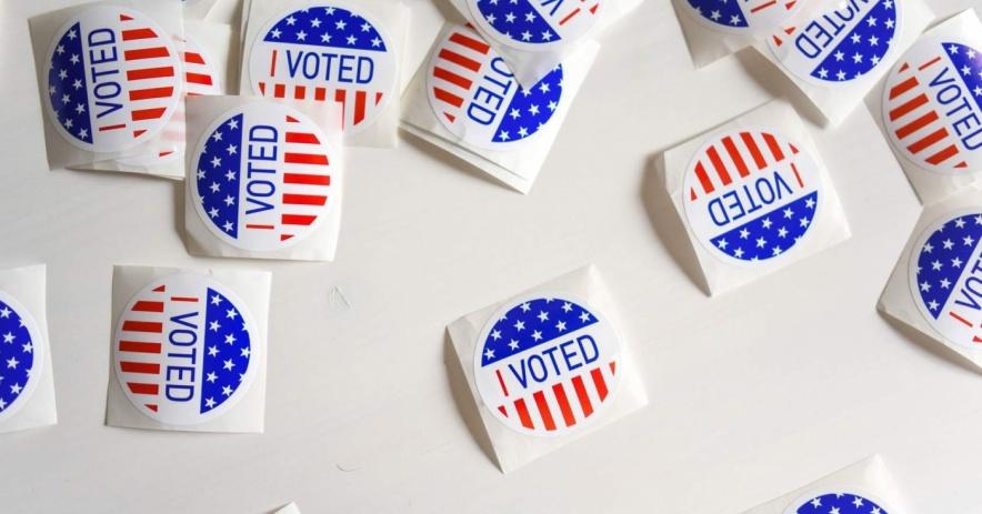"""Pegatinas dispersas de """"Yo voté"""" con la bandera estadounidense sobre un fondo blanco."""
