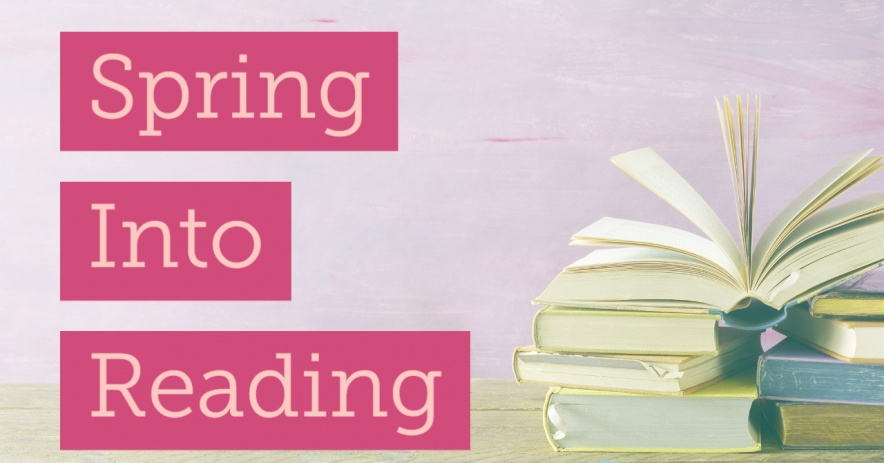 Spring into reading image with stacked books on a wooden table with a pink wall behind them.