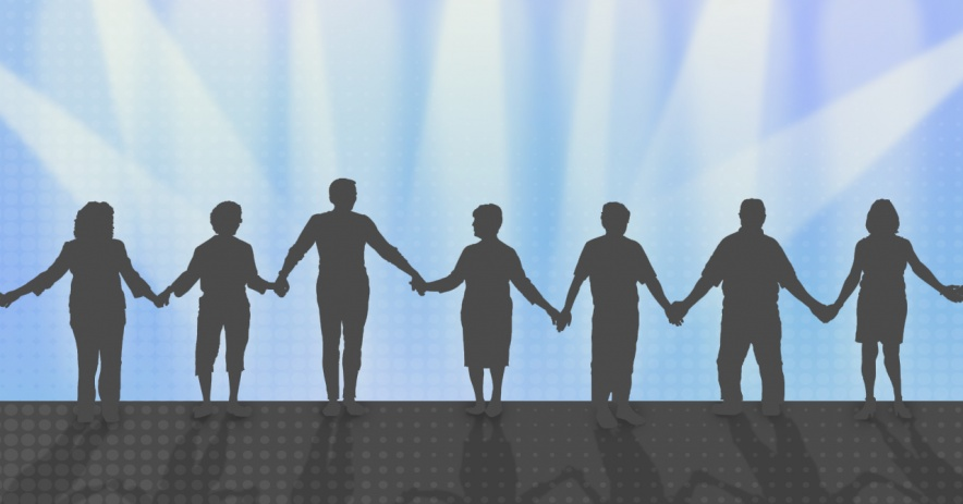 Silhouettes of seven people holding hands.