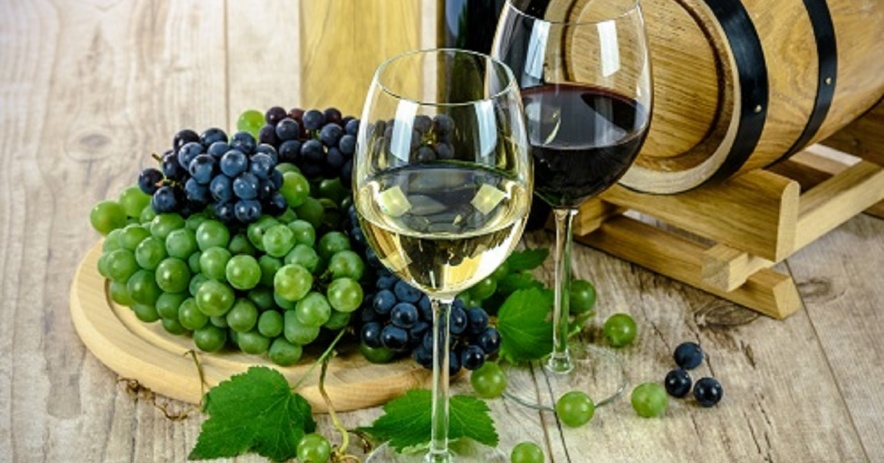 An image of two glasses of wine, one red and one white. Bunches of green and purple grapes are on a wooden plate. A small, wooden barrel rests beside the glasses of wine and grapes.