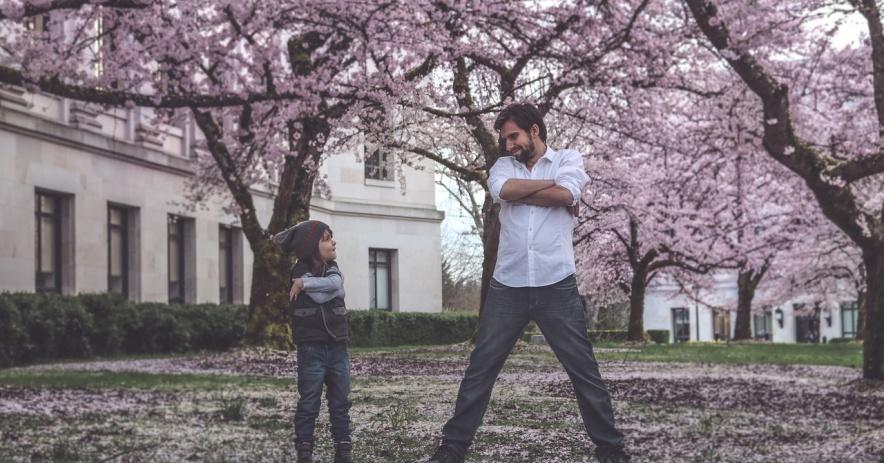 Hai cha con đứng trong tư thế ngớ ngẩn đối diện nhau trên bãi cỏ được bao quanh bởi những cây anh đào nở hồng rực rỡ.