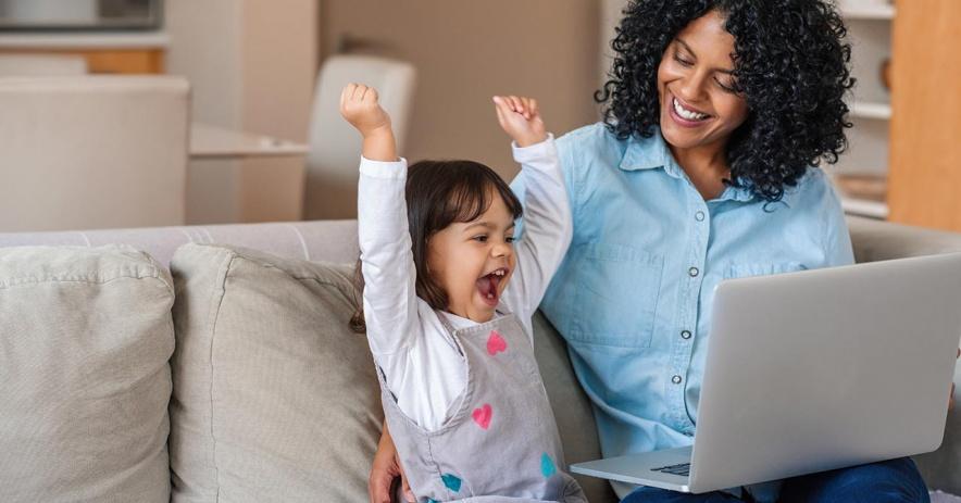 Niña emocionada mira storytime en una computadora portátil con su madre.