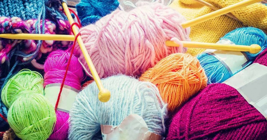 Hilo de colores y agujas de tejer.
